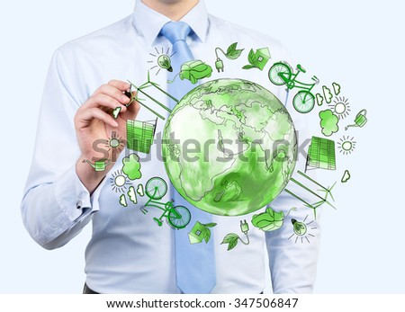 man pointing at the green picture of eco energy icons arranged in circle, earth in the centre, concept of clean and safe  environment, breast view - stock photo