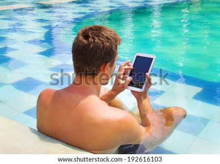 man poolside holding tablet computer - stock photo