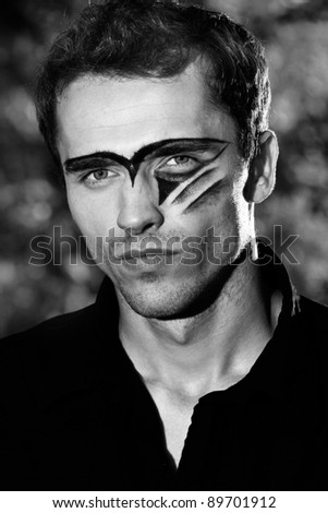 man portrait, hard handsome male model with military makeup - black and white version - stock photo
