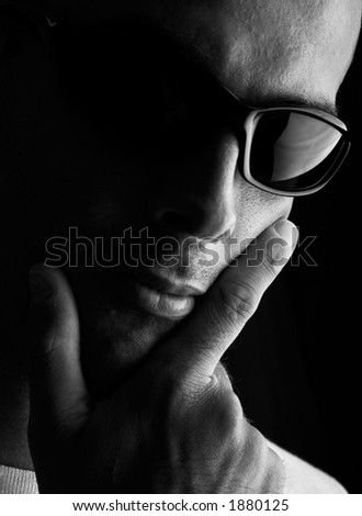 Man portrait with eyeglasses (focus in on the finger and glasses) - stock photo