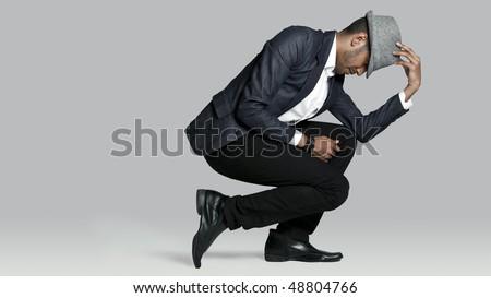 Man poses on one knee in studio - stock photo