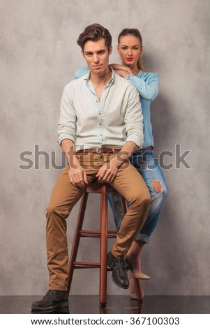 man posing in studio seated while girl in the back rests her hands on his shoulders - stock photo