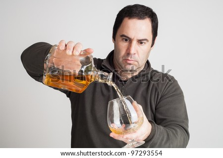man pouring  a glass of whiskey on casual clothes - stock photo