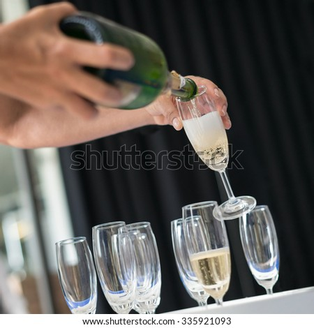 Man pouring champagne into glass, selective focus. - stock photo