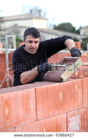 Man pouring wet cement on to wall - stock photo