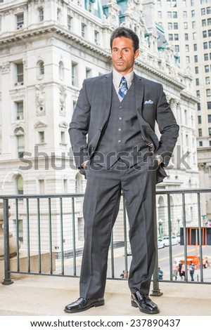 Man Power. Dressing in dark blue three piece suit, necktie, leather shoes, hands in pockets, a handsome, sexy, middle age businessman is standing outside office building, confidently looking at you. - stock photo