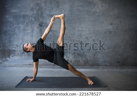 Man practicing advanced yoga against a urban background - stock photo