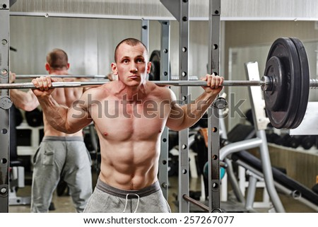 Man practicing with a barbell in the gym on the simulator - stock photo