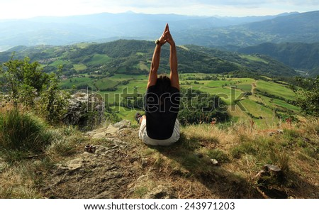 man practicing Yoga at the top of a mountain - stock photo