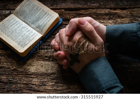 man praying before a bible selective focus - stock photo