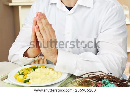 Man praying before eating - stock photo