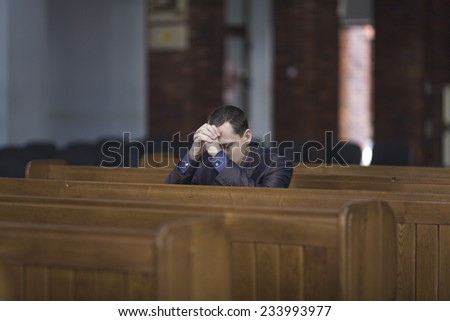 Man praying in church - stock photo