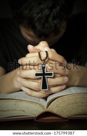 Man praying to God with bible and rosary on his hands - stock photo