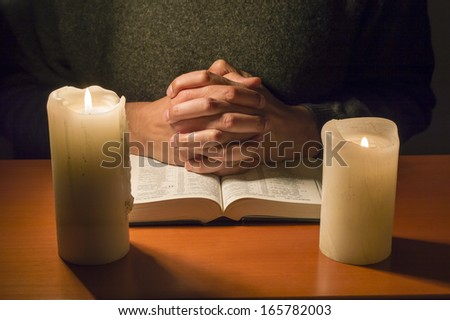 man praying with a bible in the candlelight - stock photo