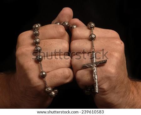 Man prays the rosary - stock photo