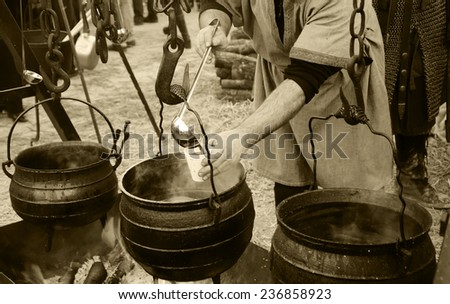 Man prepares and sells hot wine and soup at traditional Christmas Medieval fair in Provins (France). Aged photo. Sepia. - stock photo