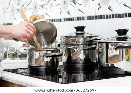 Man prepares dinner on modern induction cooker - stock photo