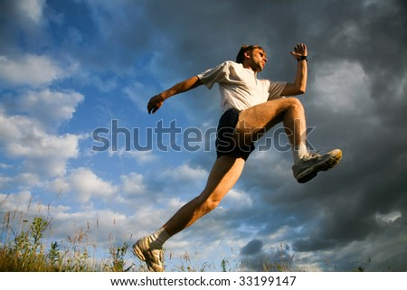 Man prepares for jump on a sky background - stock photo