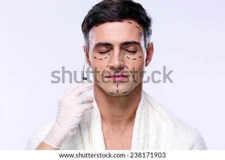 Man preparing for plastic surgery over gray background - stock photo