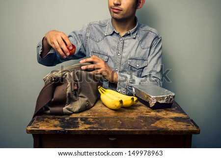 Man preparing his lunch at old desk - stock photo