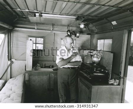 Man preparing tea inside his camping trailer - stock photo