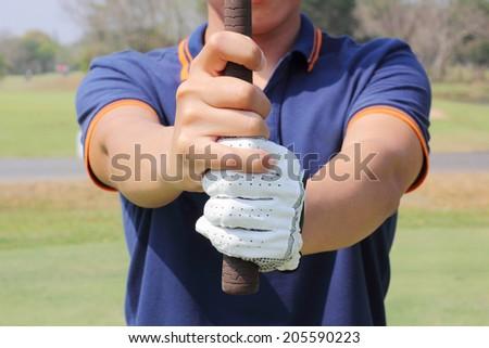 Man preparing to grip a golf club  - stock photo