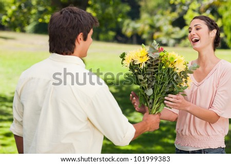 Man present his surprised friend with a bouquet of flowers in a park - stock photo