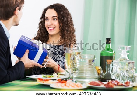 Man presenting gift to young woman during romantic dinner with champagne in home - stock photo