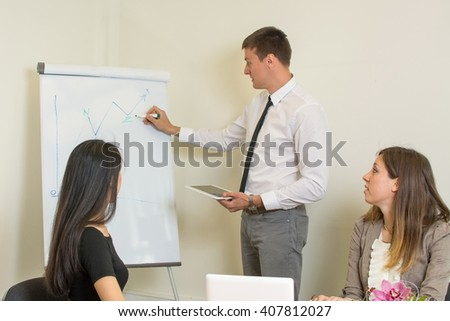 man presenting on a flipchart while colleagues listen - stock photo