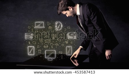 Man pressing table tablet hand touch interface with media icons and symbols - stock photo
