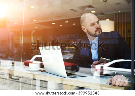Man professional broker with mobile phone in hands is waiting in cafe clients for conclusion of the transaction at the stock exchange. Male proud financier resting after conference via laptop computer - stock photo