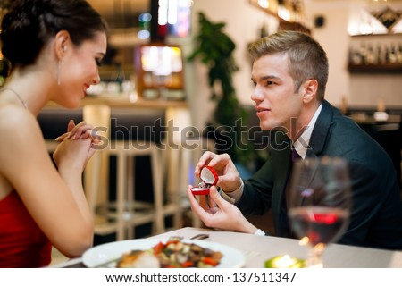 Man proposing to his girlfriend while they are having a romantic date at the restaurant - stock photo