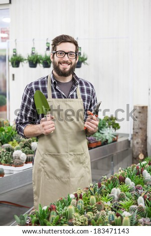 Man Pruning Small Potted Plant - stock photo
