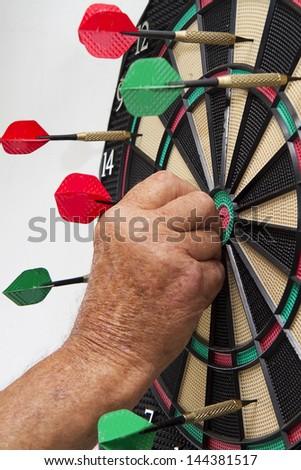 Man pulling darts of dart board - stock photo