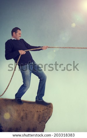 man pulling rope tug of war on a cliff edge adversity concept  - stock photo