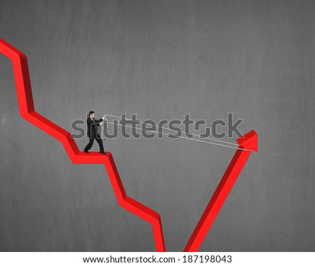 Man pulling up going down red arrow concrete wall background - stock photo