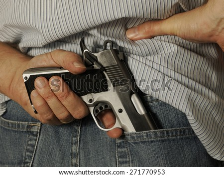 Man pulls a loaded gun from his blue jeans - stock photo