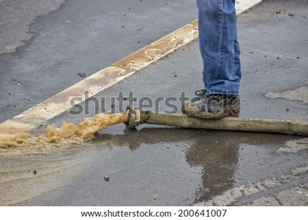 Man pumping away flood water. Flood water being pumped out of house. - stock photo