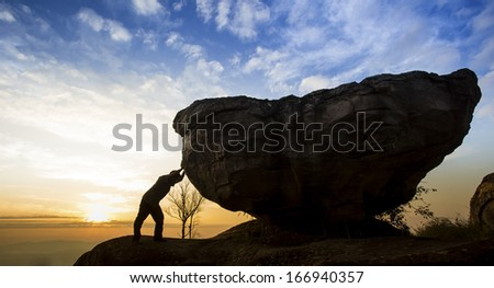 Man pushing a boulder on a rock  - stock photo