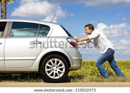 Man pushing a broken car down the road - stock photo
