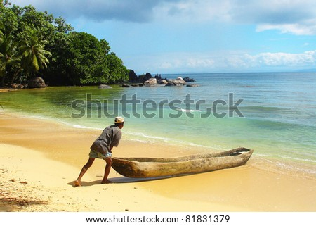 Man pushing a traditional canoe in Madagascar 					 - stock photo