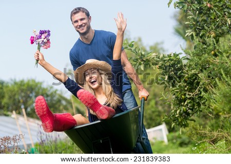 Man pushing his girlfriend in a wheelbarrow at home in the garden - stock photo