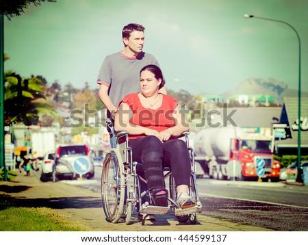 Man pushing woman in wheelchair - stock photo