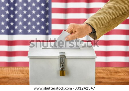 Man putting a ballot into a voting box - USA - stock photo