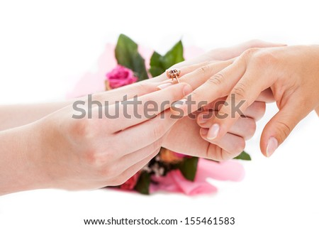 Man putting a golden ring on woman's hand, isolated background - stock photo