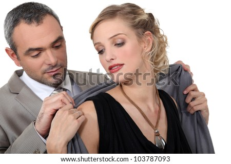 Man putting a shawl around his date's shoulders - stock photo