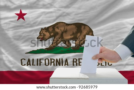 man putting ballot in a box during elections  in front of flag american state of california - stock photo