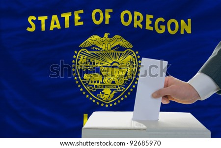 man putting ballot in a box during elections  in front of flag american state of oklahoma - stock photo