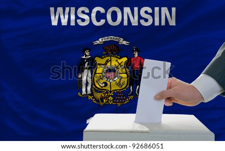 man putting ballot in a box during elections  in front of flag american state of wisconsin - stock photo