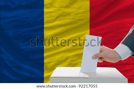 man putting ballot in a box during elections in romania in front of flag - stock photo